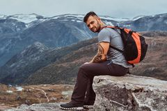 Handsome man sits on a rock in the background of a beautiful mountain landscape in Norway. Handsome bearded tourist sits on a rock in the background of a royalty free stock photo