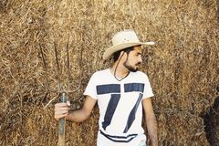 Handsome bearded young cowboy holding a pitch fork. Handsome bearded young cowboy holding a pitch fork Royalty Free Stock Image