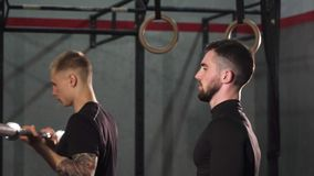 Two young male crossfit athletes working out with barbells. Handsome bearded young crossfit athlete workoing out at the gym with his friend lifting barbell. Two stock video footage