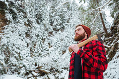 Handsome bearded young man with axe in winter forest Stock Photo