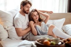 Handsome bearded young man and his beautiful brunette girlfriend spend weekend together in bedroom, eat breakfast in bed stock image
