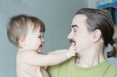 Handsome bearded young man holding infant little girl. Happy smiling father and baby daughter portrait royalty free stock images