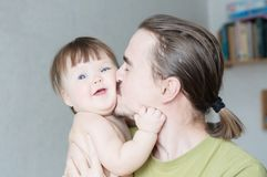 Handsome bearded young man kissing infant little girl. Happy smiling father and baby daughter portrait. Handsome bearded young men kissing infant little girl Royalty Free Stock Images