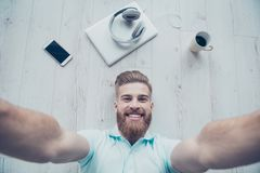 Handsome bearded young man is making selfie and smiling. He is stock photo