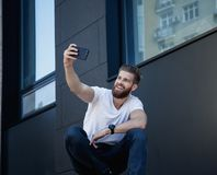 Handsome bearded young man is making selfie and smiling he is in white t shirt royalty free stock images