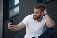 Handsome bearded young man is making selfie and smiling he is in white t shirt stock image