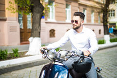 Handsome bearded young man riding blue scooter. Stock Photo