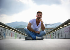 Handsome bearded young man sitting outdoors in urban environment Royalty Free Stock Images
