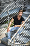 Handsome bearded young man sitting outdoors in urban environment Stock Images