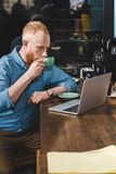Handsome bearded young man using laptop and drinking coffee. In cafe stock photo