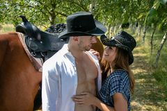 Handsome, beautiful Cowboy and cowgirl couple with horse and saddle on ranch holding and kissing on ranch royalty free stock images