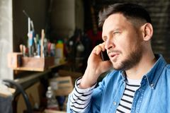 Handsome Beraded Man Speaking by Phone. Head and shoulders  portrait of handsome mature  man speaking by phone while standing in barn-like workshop, copy space Stock Photos