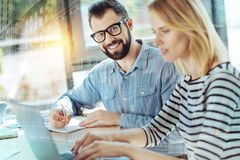 Handsome bespectacled man looking straight and writing. Best work. Handsome glad bespectacled men sitting in the room by the table near his colleague looking Stock Photos