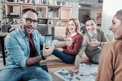 Handsome bespectacled man showing the cellphone and smiling. Look, its true. Handsome bespectacled unshaken men sitting on the floor in circle of friends Royalty Free Stock Photos
