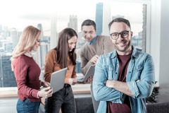 Handsome bespectacled man standing holding crossed his hands. My best colleagues. Handsome bespectacled confident men standing in the room near his colleagues Royalty Free Stock Images