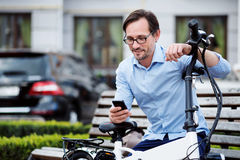 Handsome bespectacled man using cellphone. Virtual communication. Handsome bespectacled man putting his hands on bike and using laptop while sitting on the Royalty Free Stock Photo
