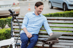 Handsome bespectacled man using laptop. Pleasure work time . Satisfied handsome man working on laptop and smiling while sitting on the bench Royalty Free Stock Photo