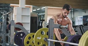 A handsome big muscular man is putting more weights into the bar , as he is being healthy and working out. 4k stock footage