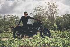 Handsome biker man in black wear sit on classic style cafe racer motorcycle. custom made motorcycle. Outdoor portrait royalty free stock photos