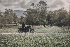 Handsome biker man in black wear sit on classic style cafe racer motorcycle. custom made motorcycle. Outdoor portrait royalty free stock images