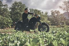 Handsome biker man in black wear sit on classic style cafe racer motorcycle. custom made motorcycle. Outdoor portrait stock images