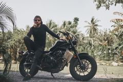 Handsome biker man in black wear sit on classic style cafe racer motorcycle. custom made motorcycle. Outdoor portrait stock image