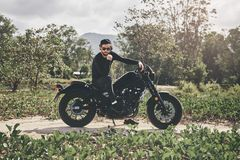 Handsome biker man in black wear sit on classic style cafe racer motorcycle. custom made motorcycle stock photo