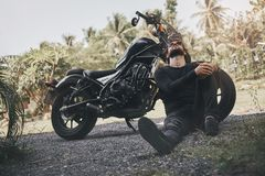 Handsome biker man in black wear sit near classic style cafe racer motorcycle. custom made motorcycle. Outdoor portrait royalty free stock photography