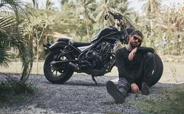 Handsome biker man in black wear sit near classic style cafe racer motorcycle. custom made motorcycle. Outdoor portrait stock images