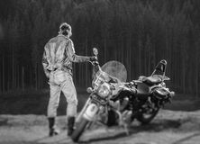 Handsome biker standing by his custom made cruiser motorcycle. Long haired brutal biker standing near his custom made cruiser motorcycle, wearing leather jacket Royalty Free Stock Image
