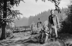 Handsome biker standing by his custom made cruiser motorcycle. Young handsome biker standing by his custom made cruiser motorcycle on a sunny day with forest on Stock Photography