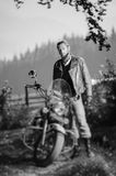 Handsome biker standing by his custom made cruiser motorcycle. Young handsome biker standing by his custom made cruiser motorcycle on a sunny day with forest on Royalty Free Stock Images