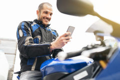 Handsome biker using mobile phone. Stock Photos