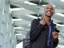 Handsome black businessman traveling with bag and cell phone. Portrait of a handsome young black businessman traveling with bag and cell phone Stock Images