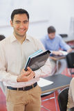 Handsome black haired teacher posing in his classroom holding some files Stock Photos