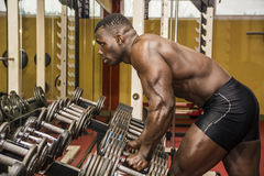 Handsome black male bodybuilder resting after workout in gym Stock Image