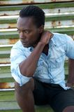 Handsome black male model sitting outdoors. Portrait of a handsome black male model sitting outdoors Stock Image