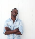Handsome black man with arms crossed, leaning against white background Stock Image