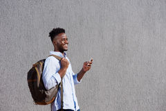 Handsome black man with bag and cellphone walking by wall Stock Photos