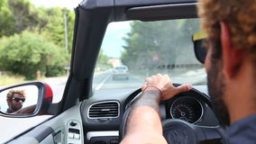 Handsome black man holding his left hand on the steering wheel of a convertible stock video footage