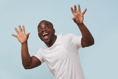 Handsome black man looking at camera and smiling, against pale blue background. Handsome bold black man in white T-shirt is smiling, against pale blue background stock photography