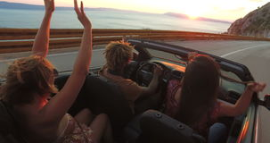 Handsome black man partying with friends while driving in convertible at sunset stock video
