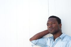 Handsome black man with relaxing against white background Stock Images