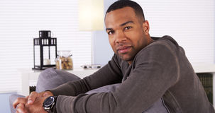Handsome black man resting on couch Stock Images