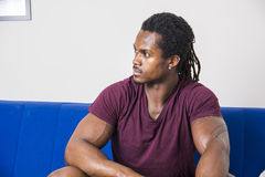 Handsome black man sitting on couch Royalty Free Stock Photos