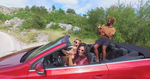 Handsome black man sitting on hood of convertible car dancing with his friends. Handsome black man with blond dreadlocks sitting on hood of convertible car and stock video footage