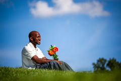Handsome black man waiting for date with flowers Stock Images