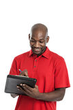 Handsome black man writing on clipboard Stock Images