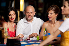 Handsome blackjack player with two elegant women Royalty Free Stock Images