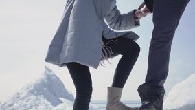 Handsome blond bearded man giving hand to attractive young woman helping her to climb on the ice block. A couple of. Handsome blond bearded man giving hand to an stock footage